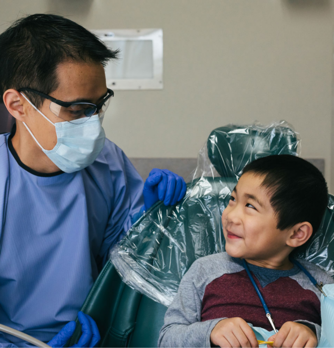 Dentist in mask looking at child patient