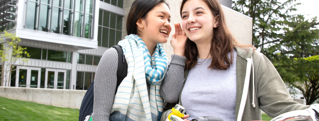 Young person smiling and whispering into the ear of another young person
