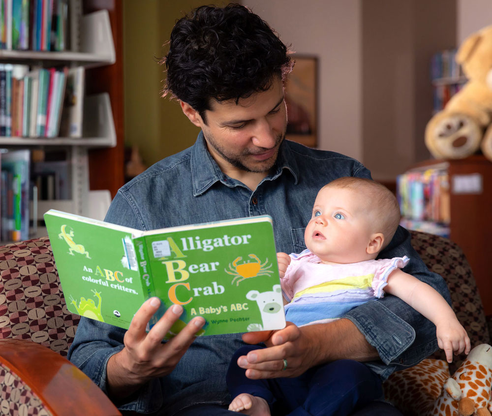 Person reading book to baby