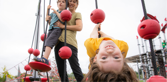 Child hanging upside down on playground equipment