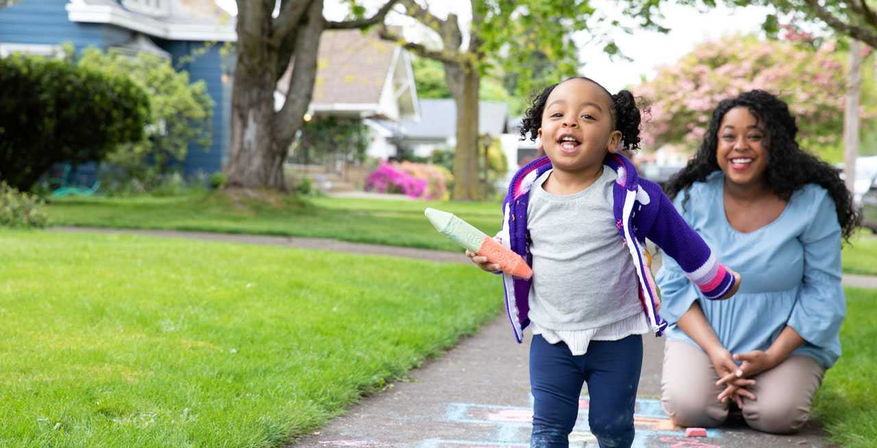 Child holding chalk crayon runs toward camera while person smiles in background