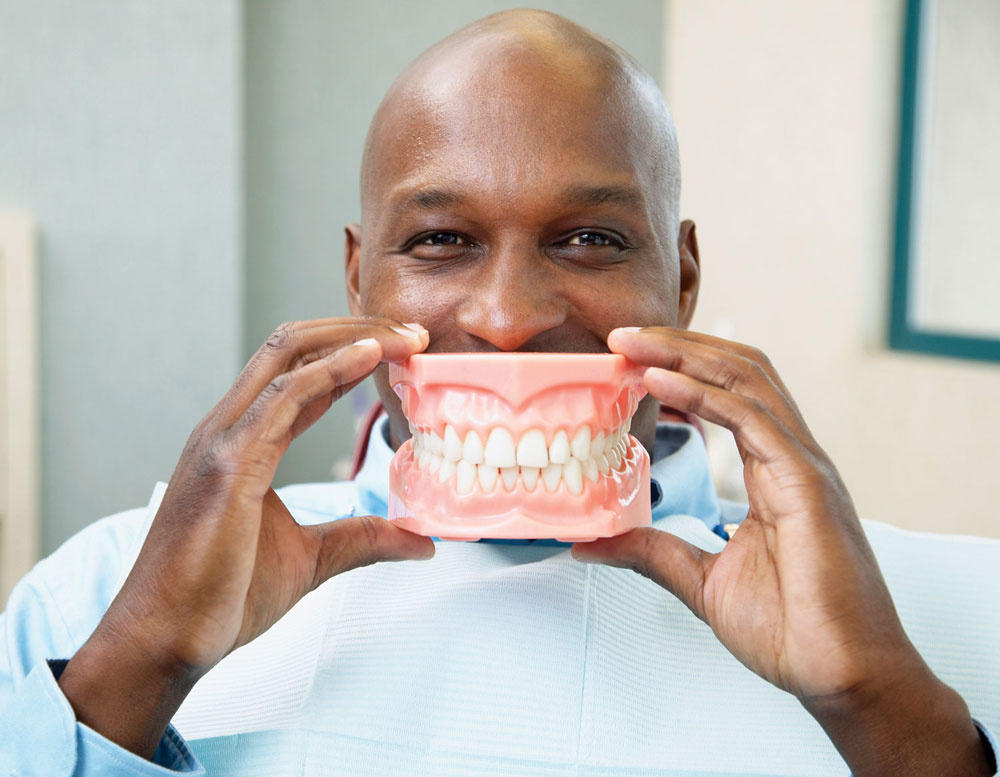 Person holding fake teeth in front of mouth