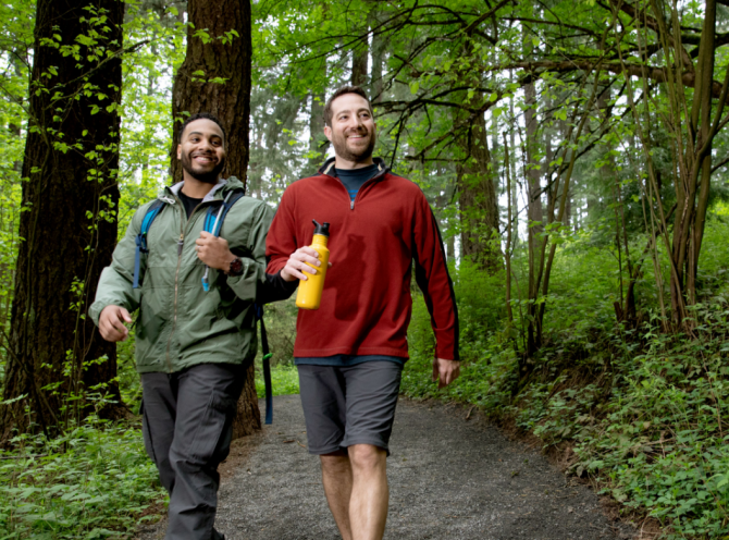 Two people smiling and walking in a forest