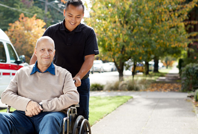 Smiling person in wheelchair being pushed by another person
